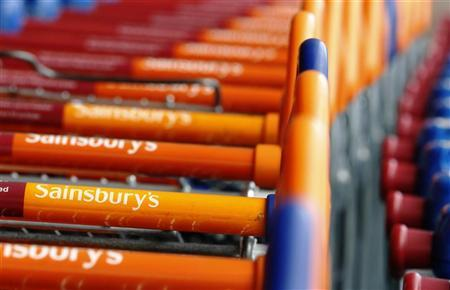 Shopping trolleys are lined up in front of a Sainsury's supermarket in London