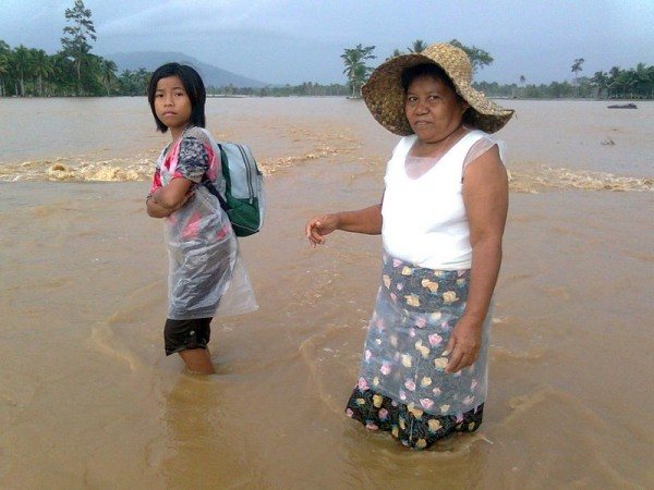 Residents wade through a flooded road in