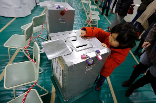 Haruka Tobe casts a ballot for her parents at a polling station in Tokyo