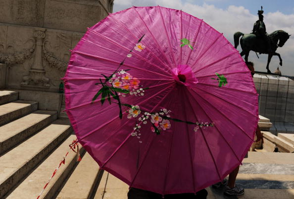 A tourist holds a Chinese umbrella to pr