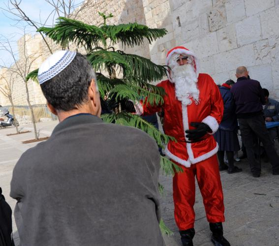 An-Israeli-Jew-watches-Palestinian-Christian-Issa-Kassissieh-wearing-a-Santa-Claus-costume-distribute-Christmas-trees-outside-the-Jaffa-Gate-in-Jerusalems-Old-City_6