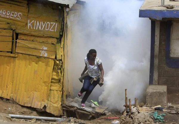 A woman escapes from a cloud of tear gas thrown by the police during the second day of skirmishes in Nairobi